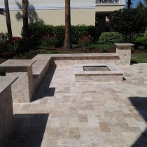 Travertine paver patio with fire pit and sitting wall with colums and wall cap deland sanford palm coast